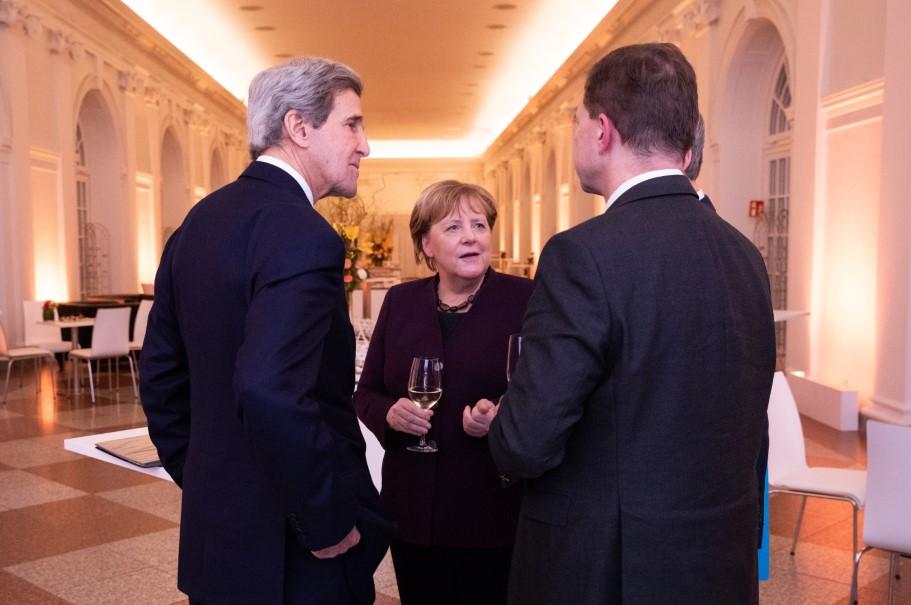 John Kerry, Angela Merkel, and German government's spokesperson Steffen Seibert speak after the Kissinger Prize ceremony. Photo: Annette Hornischer
